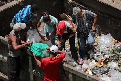 Personas buscan comida en un contenedor de basura durante la hora de cierre en el mercado mayorista de Coche el 31 de julio de 2020 (REUTERS/Manaure Quintero/File Photo)