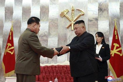 En esta imagen del domingo 26 de julio de 2020 proporcionada por el gobierno norcoreano, el dictador de Corea del Norte, Kim Jong-un, en el centro, entrega una pistola conmemorativa a un oficial del Ejército durante una ceremonia en Pyongyang. A la derecha se ve la influyente hermana de Kim, Kim Yo-jong (AP)