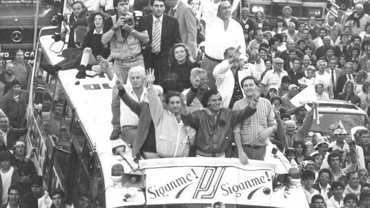De caravana con el Menemóvil: Eduardo Duhalde, Carlos Menem y Miguel Ángel Toma. Detrás, en tercera fila, Claudia Bello. A su lado, de pie, camisa blanca, Carlos Grosso