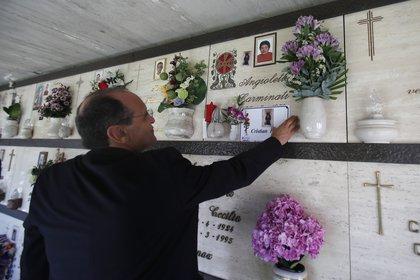El sacerdote Mario Carminati toca una foto de su sobrino Christian Persico, quien murió por síntomas de coronavirus, en un cementerio en Casnigo, cerca de Bérgamo, Italia, el domingo 27 de septiembre de 2020. (Foto AP / Antonio Calanni)