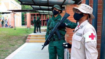 Un militar y un miliciano en la entrada de un centro electoral
