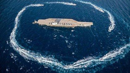 Las lanchas rápidas de la Guardia Revolucionaria giran en torno a una réplica de portaaviones durante un ejercicio militar (AP)