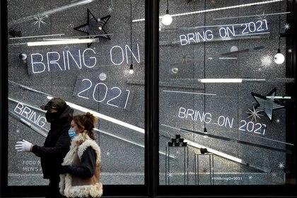Imagen de archivo de hombres enmascarados pasando por un escaparate en Londres, Inglaterra.  20 de diciembre de 2020. REUTERS / Toby Melville