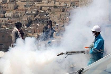La gente se cubre el rostro mientras un trabajador de la salud fumiga una zona residencial durante una campaña de fumigación mientras continúa la propagación de la enfermedad coronavirus (COVID-19), en las afueras de Sanaa, Yemen, el 13 de abril de 2020. REUTERS/Khaled Abdullah
