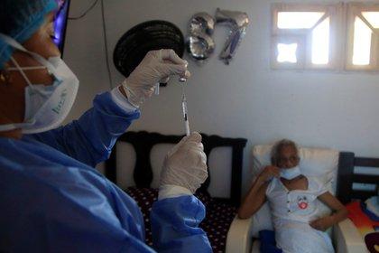 Una enfermera prepara una dosis de la vacuna Sinovac contra la covid-19 para inmunizar a una señora mayor de 80 años. EFE/RICARDO MALDONADO ROZO/Archivo