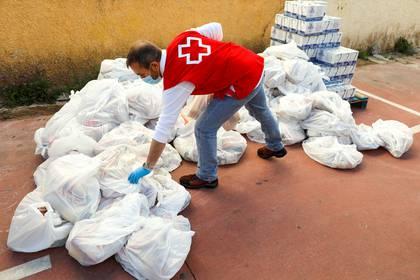 Un miembro de la Cruz Roja Española prepara alimentos para familias necesitadas en un banco de alimentos, como parte de una campaña especial de distribución durante el brote de COVID-19 en Ronda, al sur de España, el 3 de abril de 2020. (REUTERS/Jon Nazca)