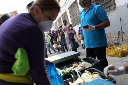 Personas con mascarillas hacen fila en un mercado de vegetales, durante la cuarentena por el brote de coronavirus, en Caracas, Venezuela. 23 de abril de 2020. REUTERS/Manaure Quintero