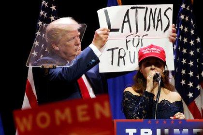 Trump mostrando un cartel de apoyo de las mujeres hispanas durante un acto en Las Vegas. REUTERS/Carlo Allegri