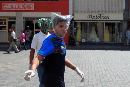 Dos ciudadanos se protegen con bolsas de plástico en Caracas (REUTERS/Carlos Jasso)
