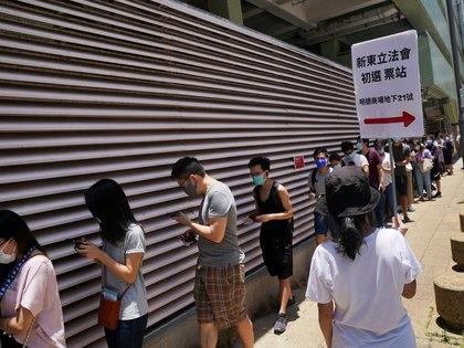 People wearing face masks following the coronavirus disease (COVID-19) outbreak line up to vote in the primary election aimed at selecting democracy candidates for the September election, in Hong Kong, China July 12, 2020.  REUTERS/Lam Yik