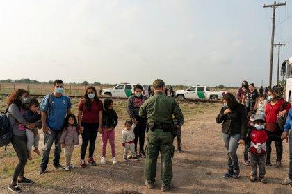 Migrantes que buscan solicitar asilo esperan a ser transportados tras cruzar el Río Grande hacia Texas (Reuters)