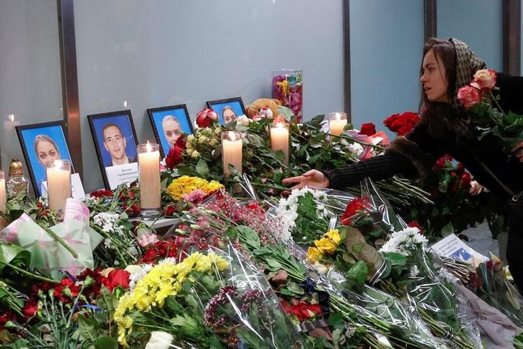 Una mujer coloca flores en un monumento en memoria de los miembros de la tripulación del avión Boeing 737-800 de Ukraine International Airlines derribado por Irán (REUTERS/Valentyn Ogirenko)