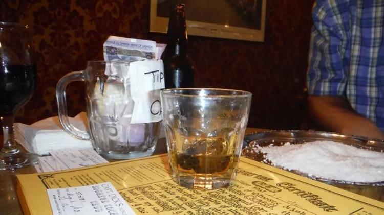 El vaso de whiskey con el dedo en su interior