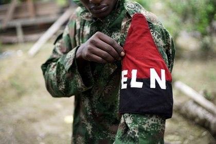 Un rebelde del Ejército de Liberación Nacional (ELN) de Colombia mostrando su brazalete mientras posa para una fotografía en la selva del noroeste de Colombia.