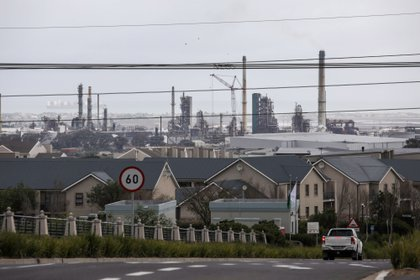 The Astron Energy Ltd., a unit of Glencore Plc, oil refinery stands beyond residential housing blocks in Cape Town, South Africa, on Thursday, July 2, 2020. At least three people died in an explosion and a fire at a South African oil refinery owned by a unit of Glencore.
