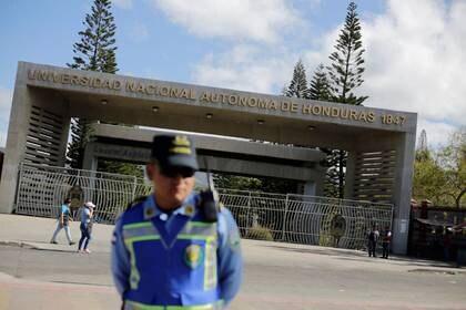 Un oficial de policía vigila la entrada de la Universidad Nacional Autónoma de Honduras, que está cerrada como parte de las medidas gubernamentales tras los primeros casos de coronavirus en el país. Tegucigalpa, Honduras. Marzo 12, 2020. REUTERS/Jorge Cabrera