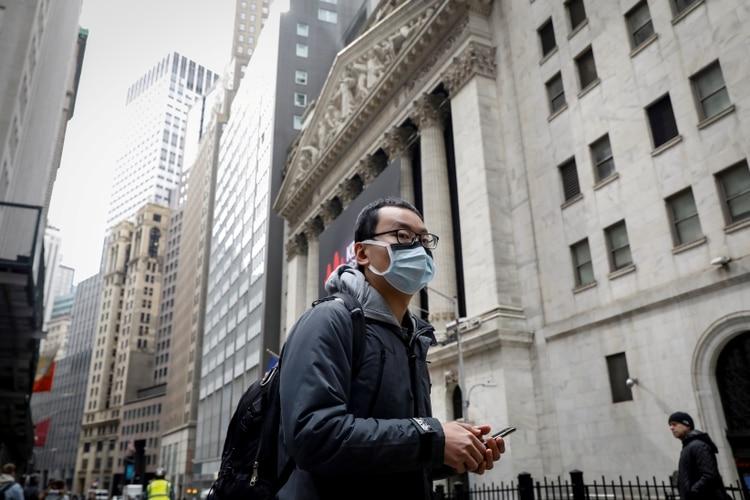 Un peatón camina con una mascarilla en las afueras de la Bolsa de Nueva York (Reuters)