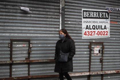 Una mujer camina frente a un comercio cerrado en Buenos Aires (EFE/Juan Ignacio Roncoroni)