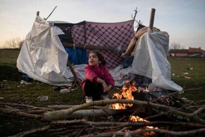 FOTO DE ARCHIVO. Una niña migrante se calienta junto al fuego cerca de las orillas del río Evros, frontera entre Turquía y Grecia, cerca de Edirne, Turquía. 3 de marzo de 2020. REUTERS/Marko Djurica.