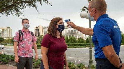 CORONAVIRUS DISNEY USA2820. LAKE BUENA VISTA (ESTADOS UNIDOS), 11/07/2020.- Fotografía sin fecha cedida por Disney donde aparece uno de sus empleados tomando la temperatura a una visitante en la entrada de una atracción en el Walt Disney World Resort en Lake Buena Vista, Florida (EEUU). EFE/Kent Phillips/Disney /SOLO USO EDITORIAL /NO VENTAS