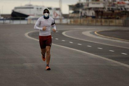 Un corredor, protegido con mascarilla, practica deporte por la capital tinerfeña este sábado tal y como ha permitido el Gobierno español para aliviar el confinamiento por el COVID-19 (EFE)