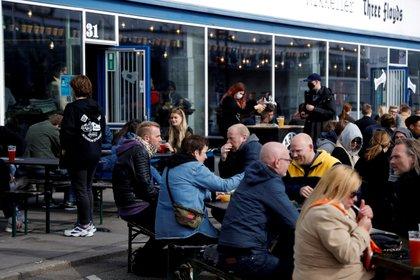 Clientes sentados afuera de un bar mientras en el centro de Copenhague, Dinamarca, el 23 de abril de 2021. Fotografía tomada el 23 de abril de 2021. REUTERS / Tim Barsoe / Foto de archivo