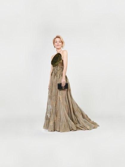 Gillian Anderson, la actriz de The Crown eligió un diseño de la última temporada de Dior de cuello halter y falda amplia de gasa y tul pintada a mano con detalles en dorado. Completó su look con pequeños aros negros, cabello recogido y maquillaje al natural  (@goldenglobes)