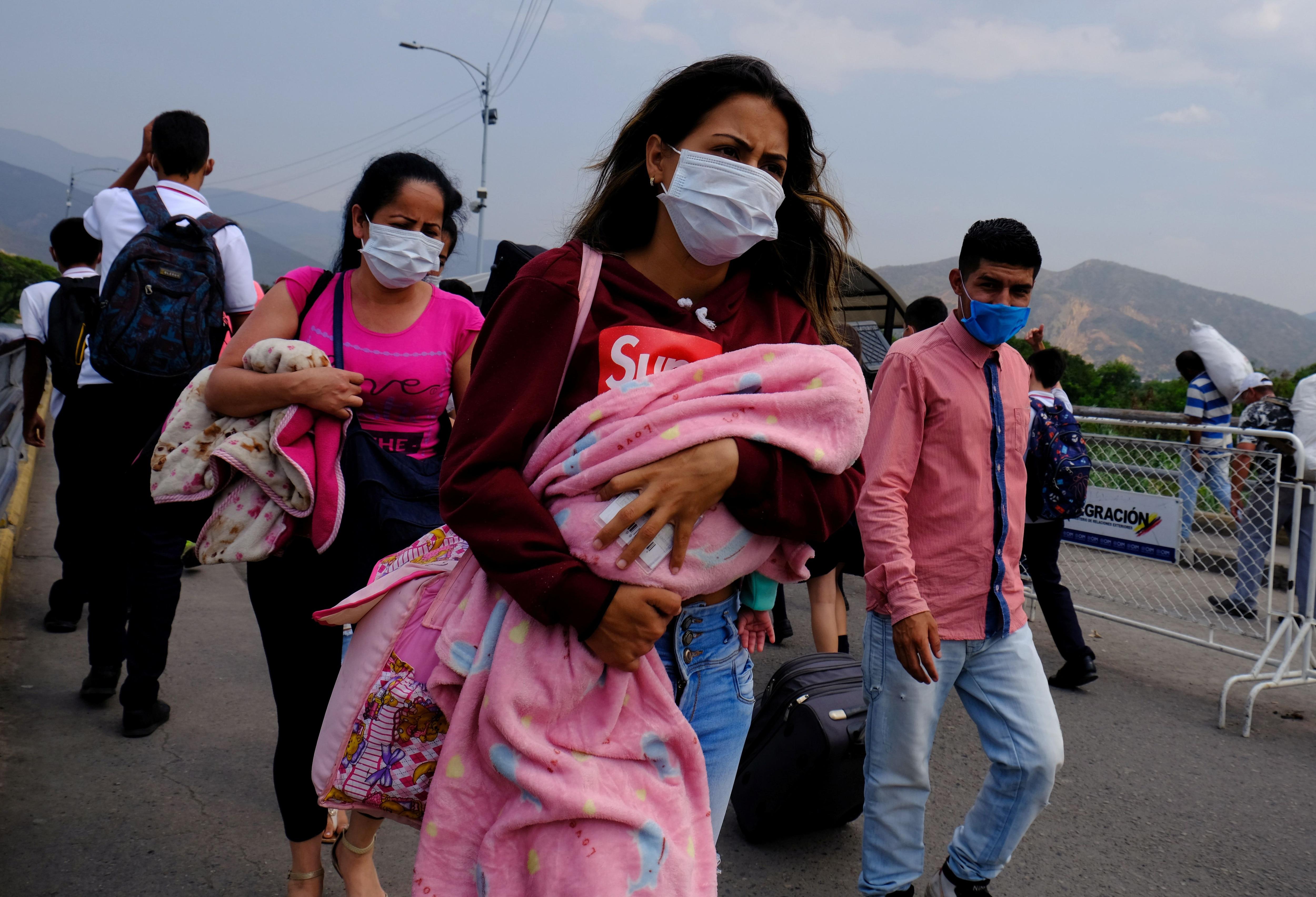 Una mujer con barbijo camina por un paso fronterizo entre Venezuela y Colombia (REUTERS/Ferley Ospina)