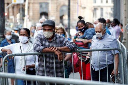 Un grupo de personas esperan en la fila para ingresar a un centro comercial, este martes, en la ciudad de Sao Paulo (Brasil). EFE/ Sebastiao Moreira