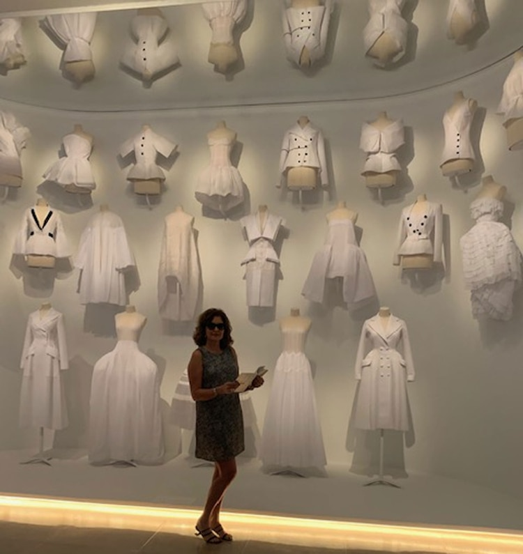 Susana Milano junto a los diseños de Dior en blanco en la exposición en Dallas