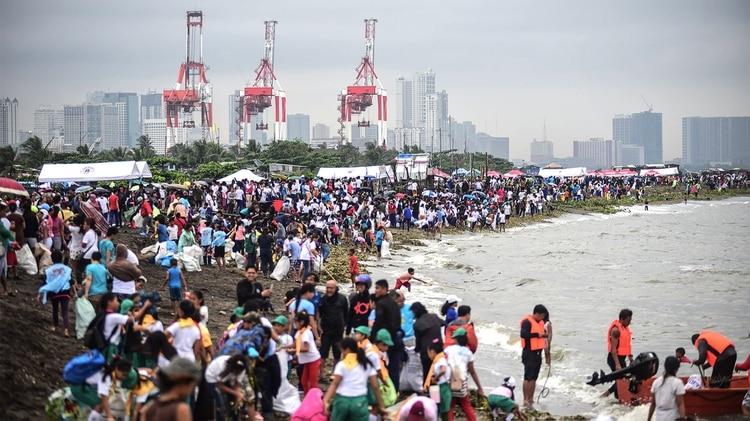Voluntarios limpian playas en Manila (AFP)
