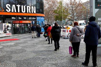 FOTO DE ARCHIVO: Compradores hacen cola frente a una tienda de electrónica Saturn en el bulevar comercial Tauentzienstrasse en Berlín, Alemania, 14 de diciembre de 2020. REUTERS/Michele Tantussi