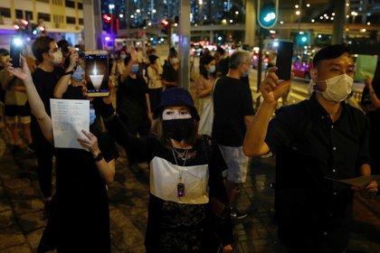 Varias personas con mascarillas protectoras levantan sus teléfonos móviles mientras participan en una ceremonia la vigilia del 31º aniversario de la sangrienta represión de las protestas en la plaza de T iananmén de Pekín de 1989, en Hong Kong, China, el 3 de junio de 2020. REUTERS/Tyrone Siu