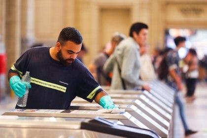 Un empleado de Trenes Argentinos limpia los molinetes como medida de precaución ante el coronavirus (REUTERS/Agustin Marcarian)