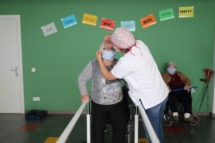 Un trabajador social le pone una máscara protectora a una anciana en un asilo (REUTERS/Nacho Doce)