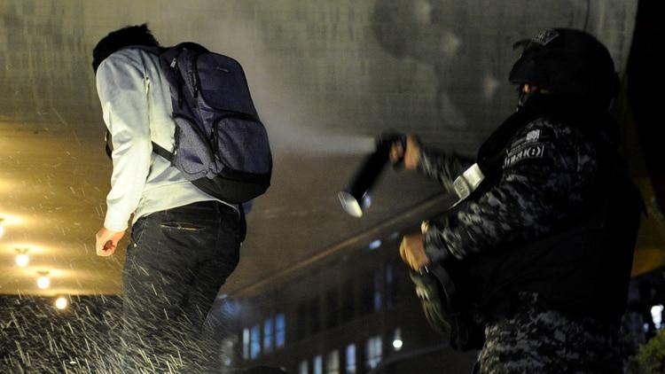 Un policía reprime a uno de los manifestantes en La Paz (Photo by JORGE BERNAL / AFP)