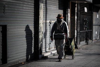 Un hombre camina frente a varios locales comerciales cerrados en Buenos Aires (Argentina). EFE/ Juan Ignacio Roncoroni/Archivo