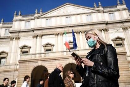 Una mujer utiliza una máscara en Milán, Italia, en medio de las prevenciones por la expansión del coronavirus en el país (REUTERS/Flavio Lo Scalzo)