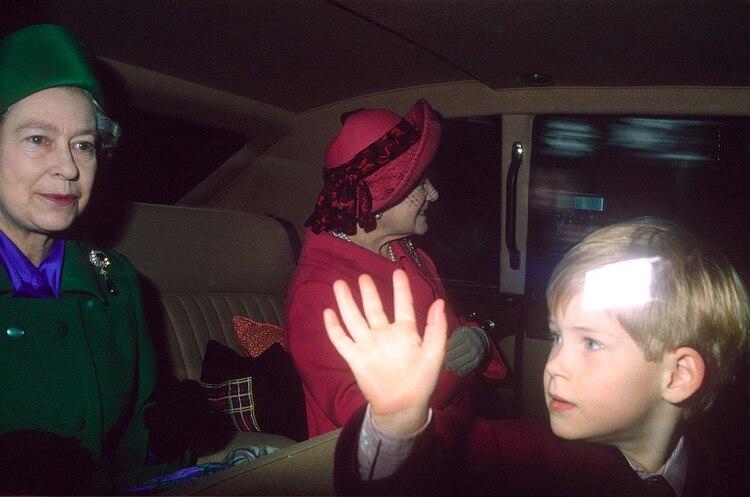 Otros tiempos. Era 1990 y la reina Isabel II lleva en su auto a un pequeño príncipe Harry. A su lado, la Reina madre (Shutterstock)