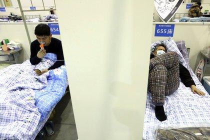 Pacientes descansan en sus camas dentro del Centro de Convenciones de Wuhan, convertido en un hospital improvisado tras el brote del nuevo coronavirus (China Daily via REUTERS)