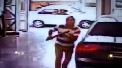 El hombre que ingresó con el hacha en el video de seguridad, detrás de él, el Chevrolet Corsa en el que huyeron