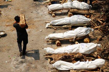 Un hombre que lleva madera pasa junto a las piras funerarias de los que murieron por la enfermedad del coronavirus (COVID-19), durante una cremación masiva, en un crematorio en Nueva Delhi, India, el 26 de abril de 2021. REUTERS/Adnan Abidi