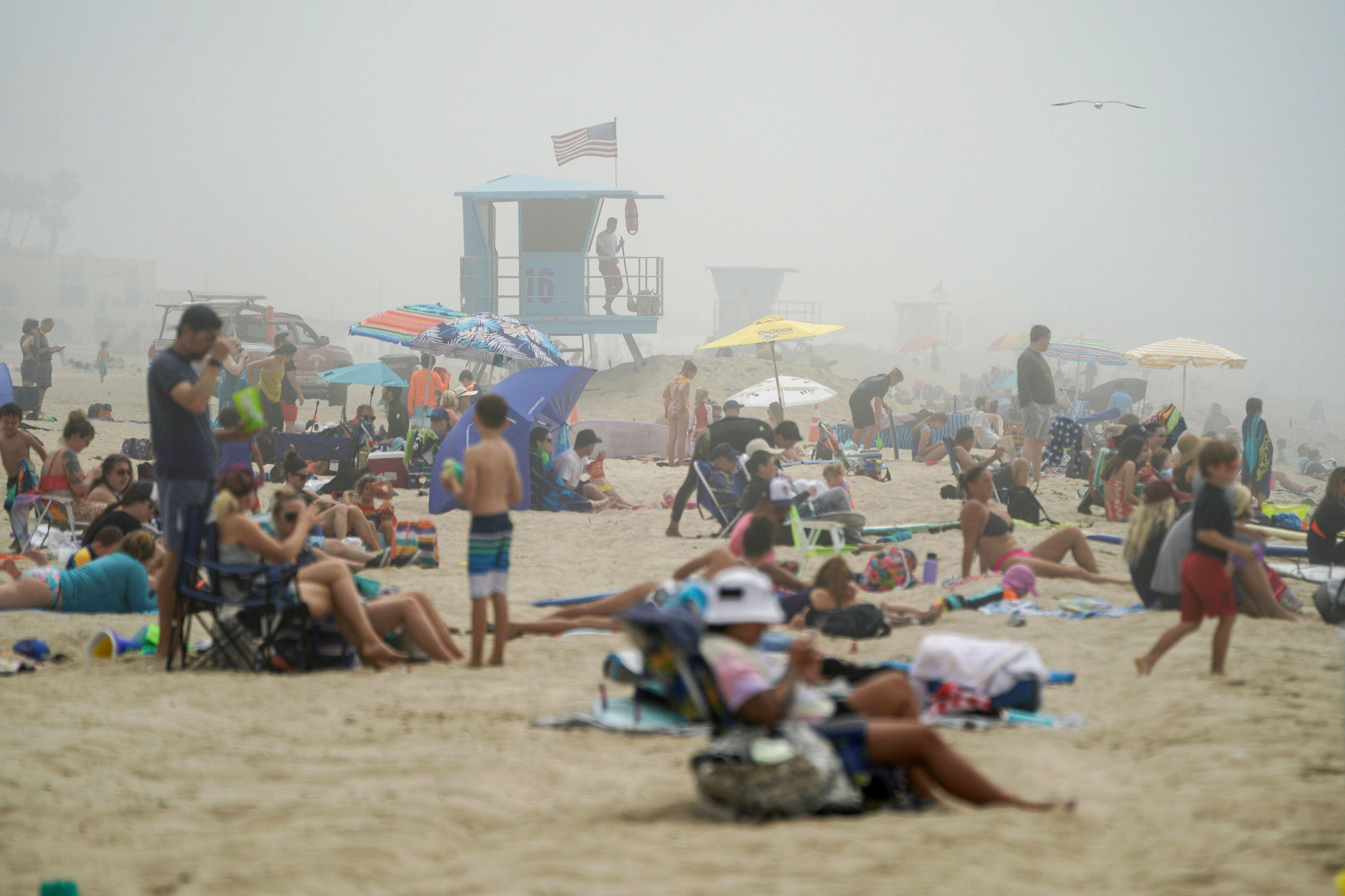 Bañistas se sientan en grupo en la playa de Huntington Beach, durante la pandemia del COVID-19, este sábado 25 de abril (Foto: REUTERS/Kyle Grillot)