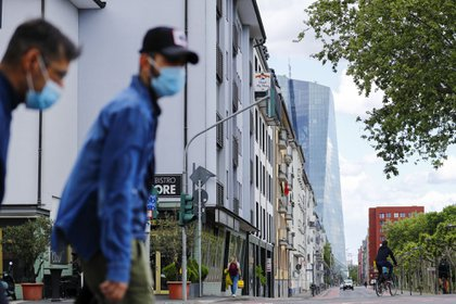 Pedestrians wearing protective face masks pass the European Central Bank (ECB) headquarters in Frankfurt, Germany, on Wednesday, April 29, 2020. The ECB's response to the coronavirus has calmed markets while setting it on a path that could test its commitment to the mission to keep prices stable.