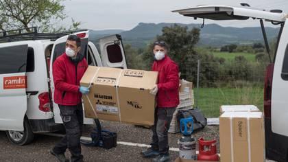 Días atrás, Toni Navarro (izquierda) le llevó aires acondicionados a su colega Jordi Morente, residente en Igualada, y recibió equipamiento para el hospital. (Samuel Aranda/The New York Times)