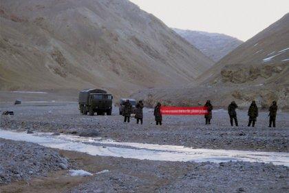 """En esta foto de archivo pueden verse a tropas chinas en la región de Ladakh, reclamada también por India, con un cartel en inglés que dice """"ha cruzado la frontera, por favor de la vuelta"""" (AP)"""