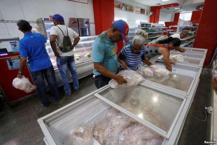 Cubanos compran pollo congelado en un supermercado de La Habana.