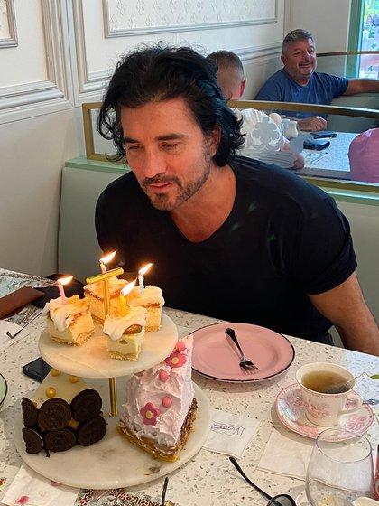 Diego pidiendo sus deseos junto a una variedad de tortas