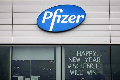 """""""Feliz año nuevo. La ciencia vencerá"""", dice el cartel en una ventana del cuartel central de Pfizer en Puurs, Bélgica."""