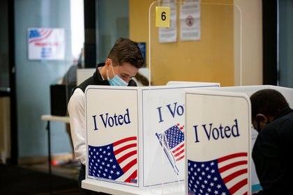 Un hombre vota con una máscara facial en un sitio de votación anticipada en Arlington, Virginia, este 18 de septiembre de 2020. REUTERS/Al Drago